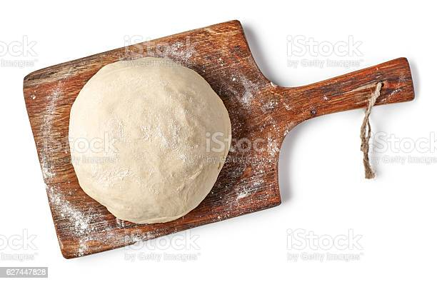 fresh raw dough on wooden board isolated on white background, top view