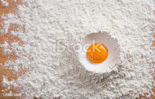 Fresh raw egg yolk in pile of white flour with copy space. Top view, horizontal close-up. Cakes, pastries, breads, bakery foods, culinary arts concepts.