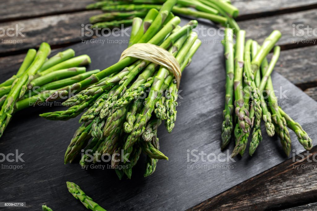 Fresh raw green Asparagus on wooden chopping board stock photo