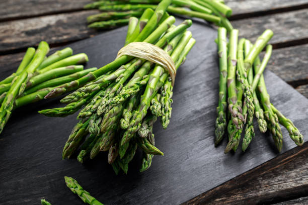 fresh raw green asparagus on wooden chopping board - asparagus stock pictures, royalty-free photos & images