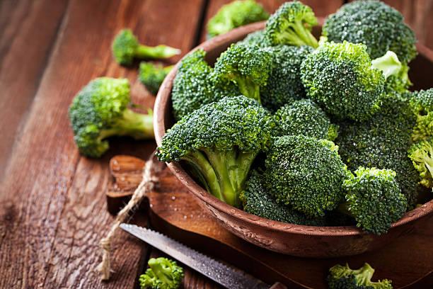 fresh raw green broccoli in bowl - broccoli stockfoto's en -beelden