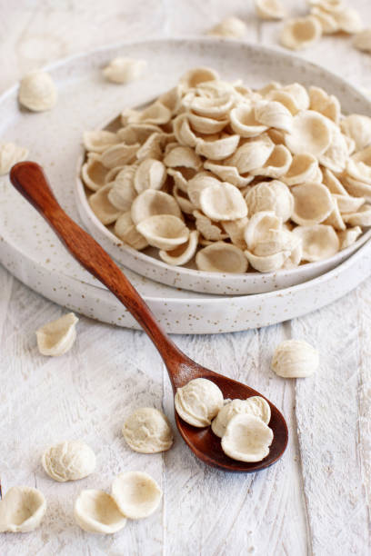 Fresh raw  italian pasta orecchiette Fresh raw apulian pasta orecchiette made from whole wheat flour on a wooden table close up orecchiette stock pictures, royalty-free photos & images