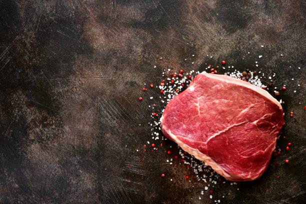 Frisches roh marmoriertes Beefsteak mit Gewürzen und Salz – Foto