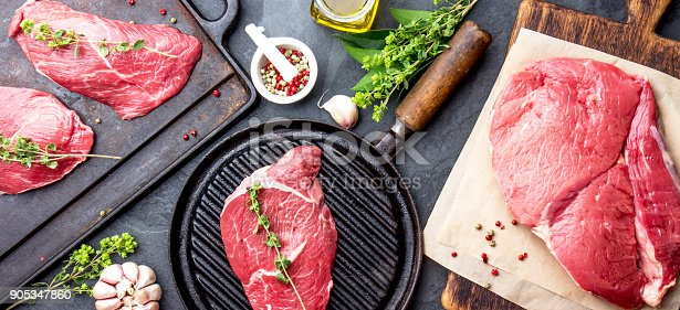 istock Fresh raw meat. Beef Tenderloin and marbled beef steaks on grill pan and frying board with seasoning, black background top view 905347860