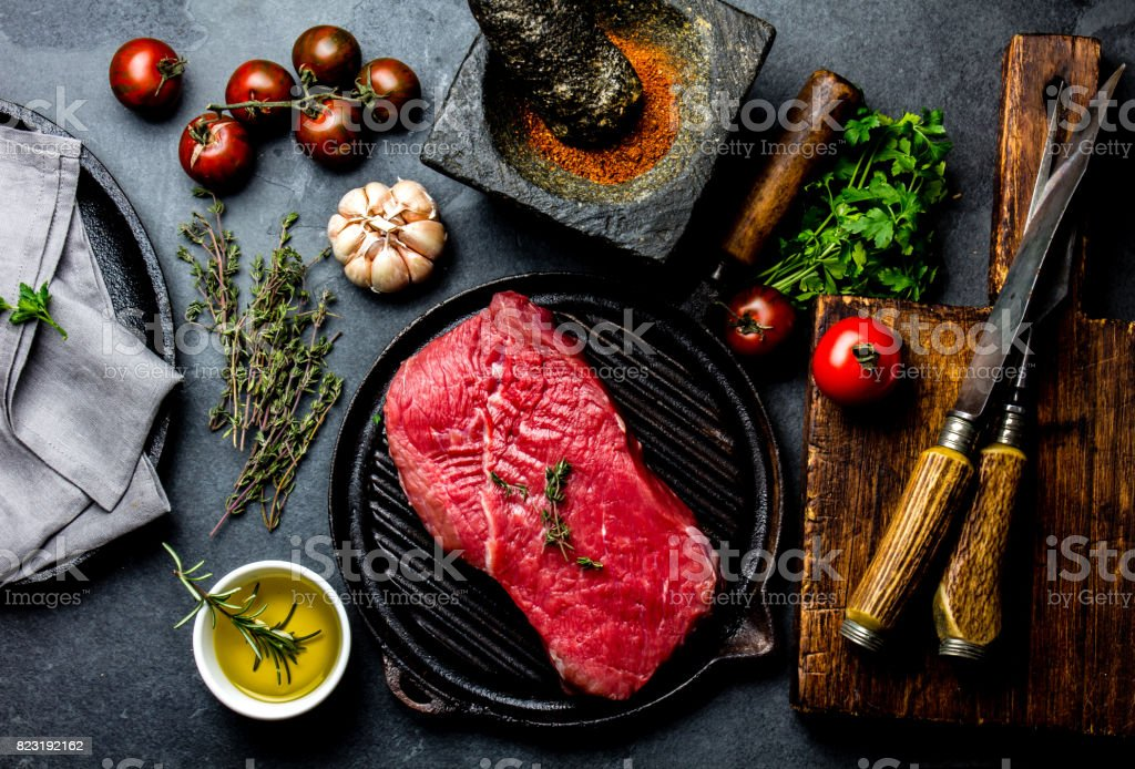 Fresh raw meat steak beef tenderloin, herbs and spices around cutting board. Food cooking background with copy space stock photo
