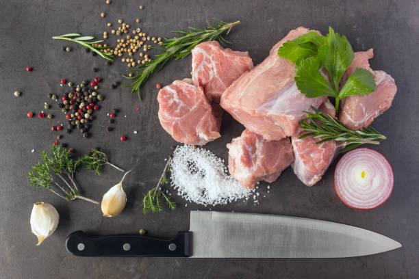 vers rauw vlees met kruiden, specerijen en een slagersmes op het oppervlak van een donkere steen ligt. - jong dier stockfoto's en -beelden