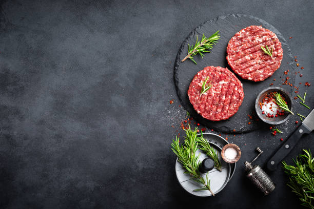 Fresh raw minced beef steak burgers with spices stock photo