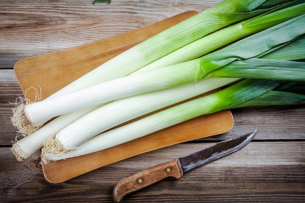 Fresh raw organic leek Fresh raw organic leek on a wooden table leek stock pictures, royalty-free photos & images