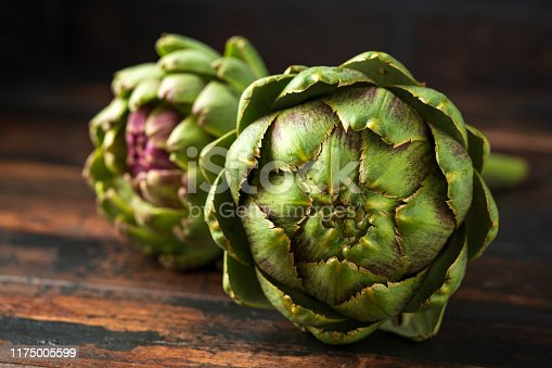 Fresh raw organically grown artichoke flower buds on wooden table.