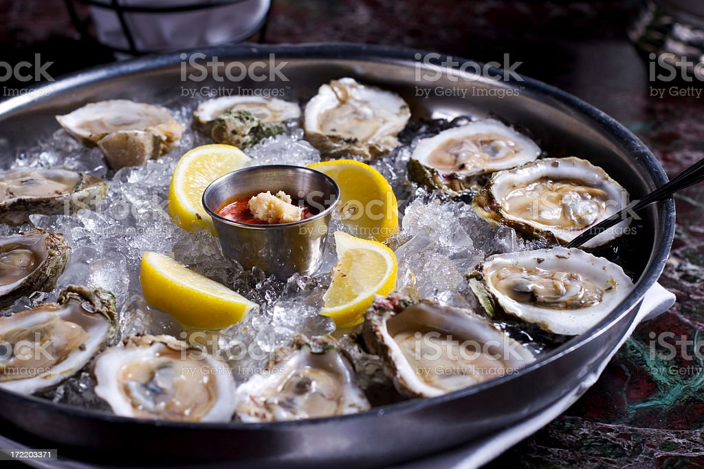 Fresh raw oysters with lemons on ice in metal tray stock photo