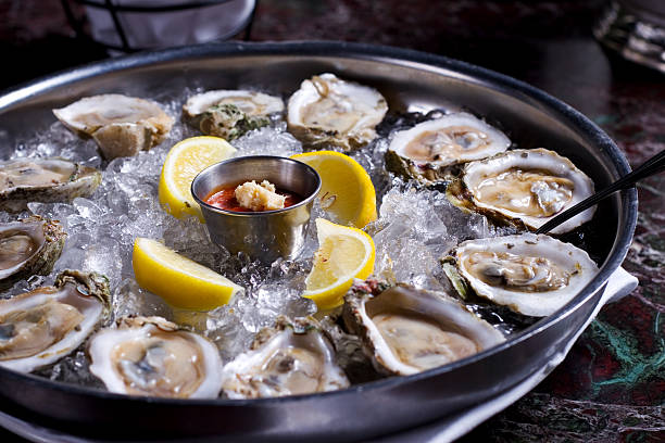 fresh raw oysters with lemons on ice in metal tray - oyster stock pictures, royalty-free photos & images