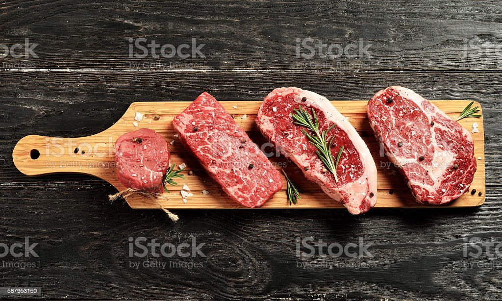 Fresh raw Prime Black Angus beef steaks on wooden board stock photo