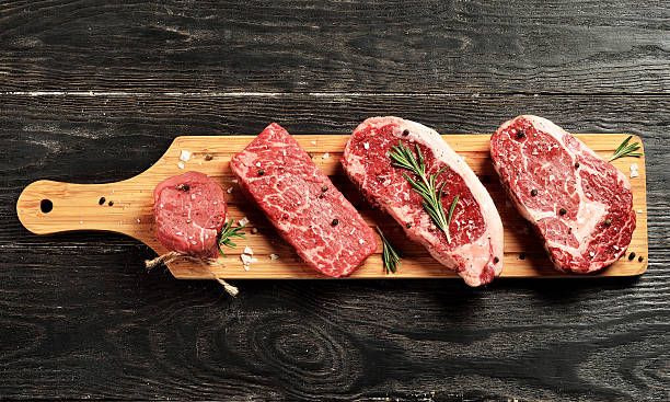 Fresh raw Prime Black Angus beef steaks on wooden board - foto de stock