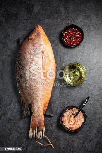 Fresh raw red snapper fish with red pepper, olive oil and Himalayan rock salt on dark background. Top view. Vertical composition.