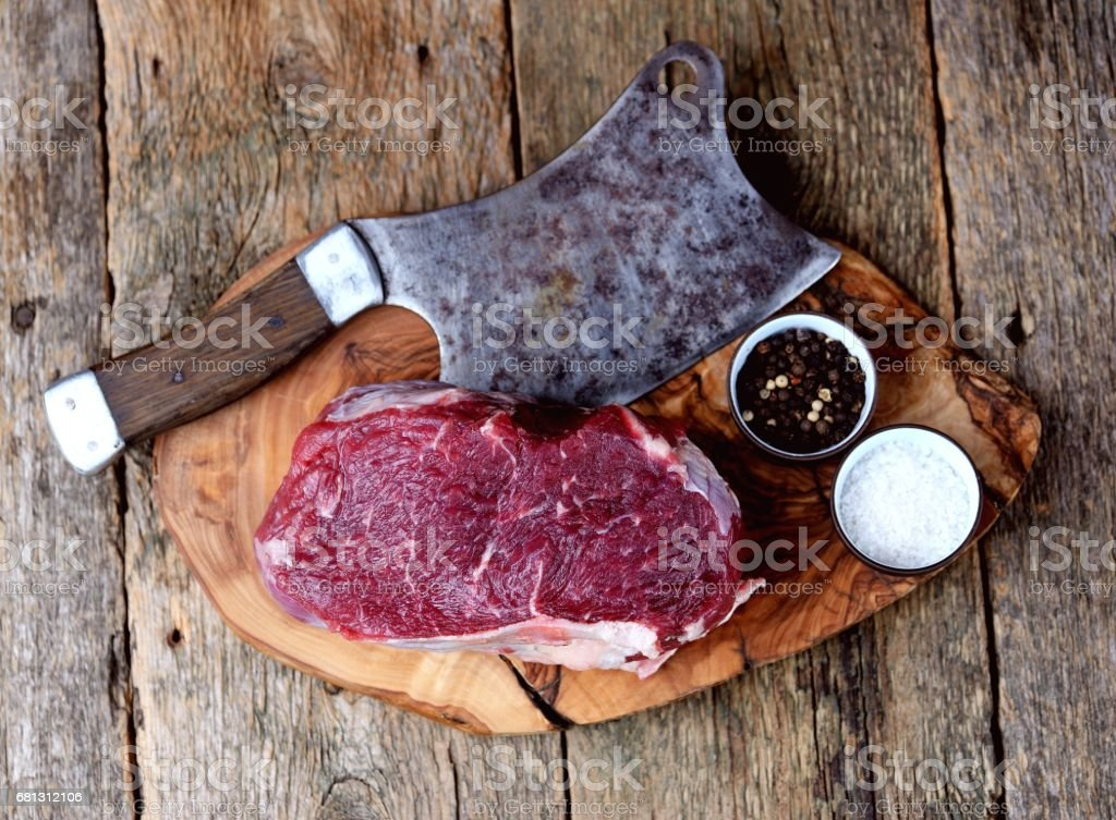 Fresh raw roast beef on a cutting board on an old wooden background. Rustic style. royalty-free stock photo