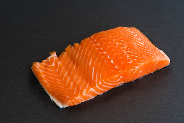 Fresh raw salmon filet on black background - foto stock