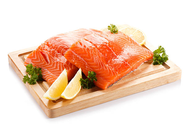 Fresh raw salmon fillet on cutting board on white background stock photo