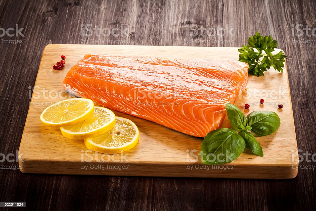 Fresh raw salmon fillet on cutting board stock photo