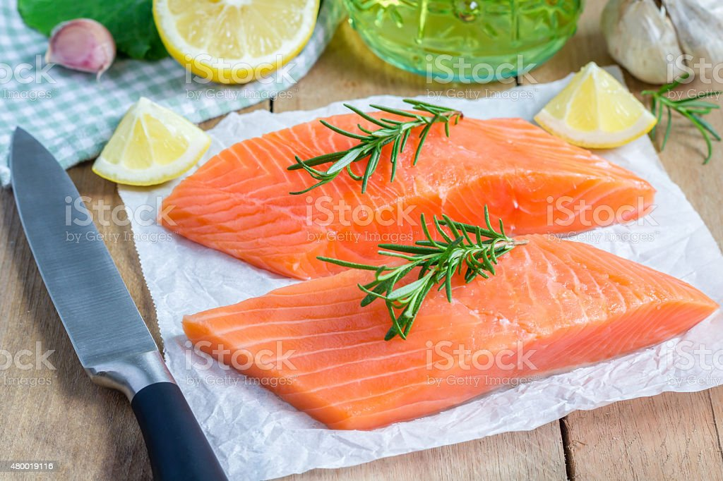 Fresh raw salmon fillet with rosemary and lemon stock photo