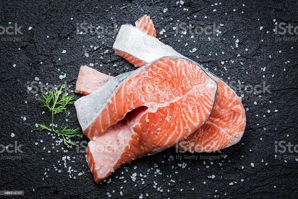 Fresh raw salmon on black rock stock photo
