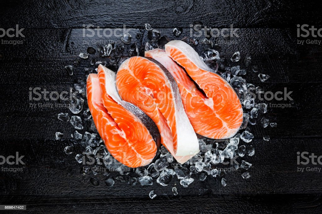 Fresh raw salmon red fish steak on ice on black wooden table top view stock photo