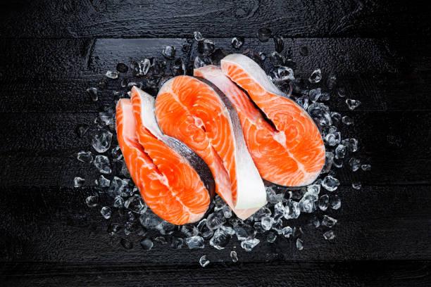Three raw salmon steaks on ice on black countertop