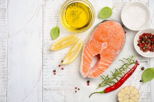 fresh raw salmon steak with lemon, olive oil and spices on rustic wooden background. - mediterranean food imagens e fotografias de stock
