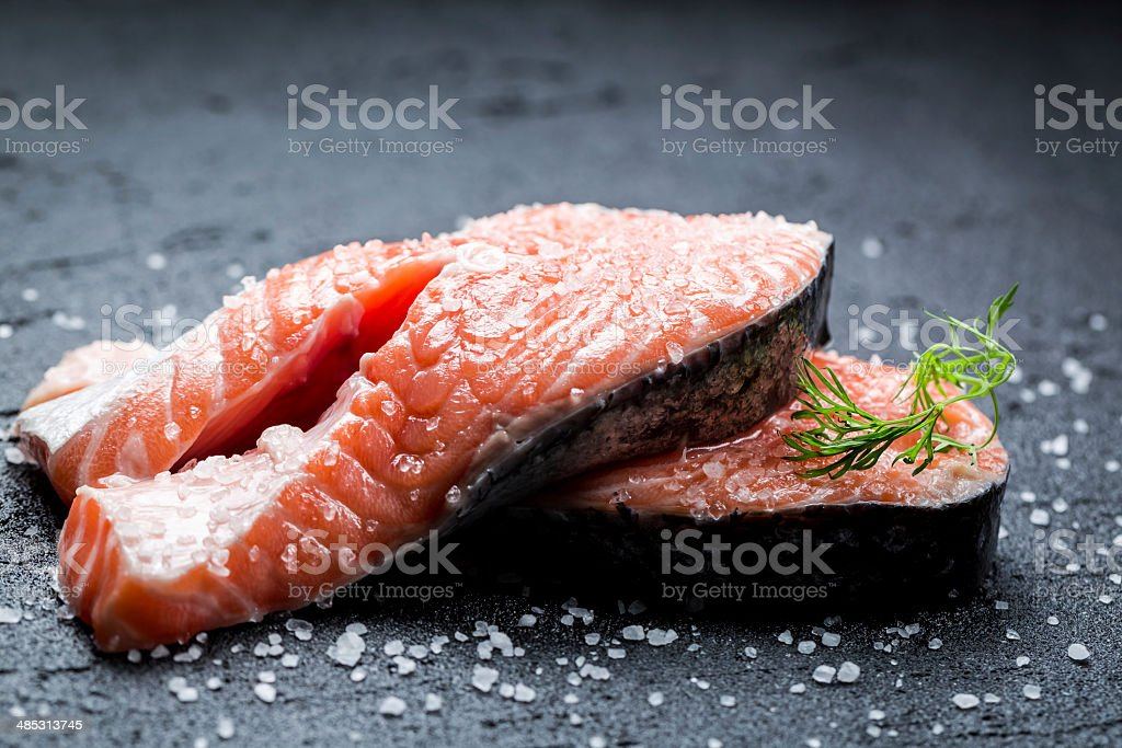 Fresh raw salmon with coarse salt stock photo