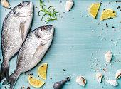 レモン スライス、ハーブおよび青い木製の背景、コピー spac で貝で飾られた新鮮な生鯛の魚