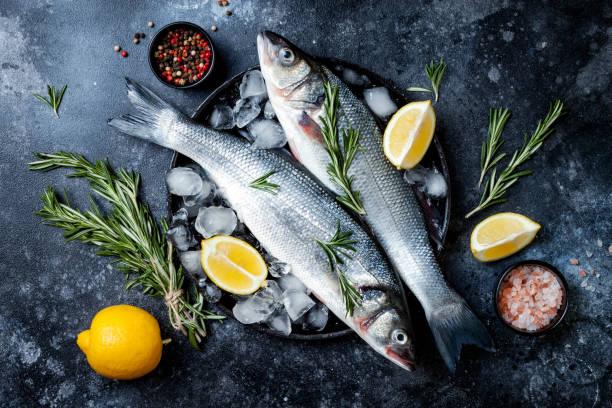 Frischer rohroter Seabass-Fisch auf schwarzem Steinhintergrund mit Gewürzen, Kräutern, Zitrone. Kulinarischer Hintergrund mit Meeresfrüchten mit Zutaten zum Kochen. Top View – Foto