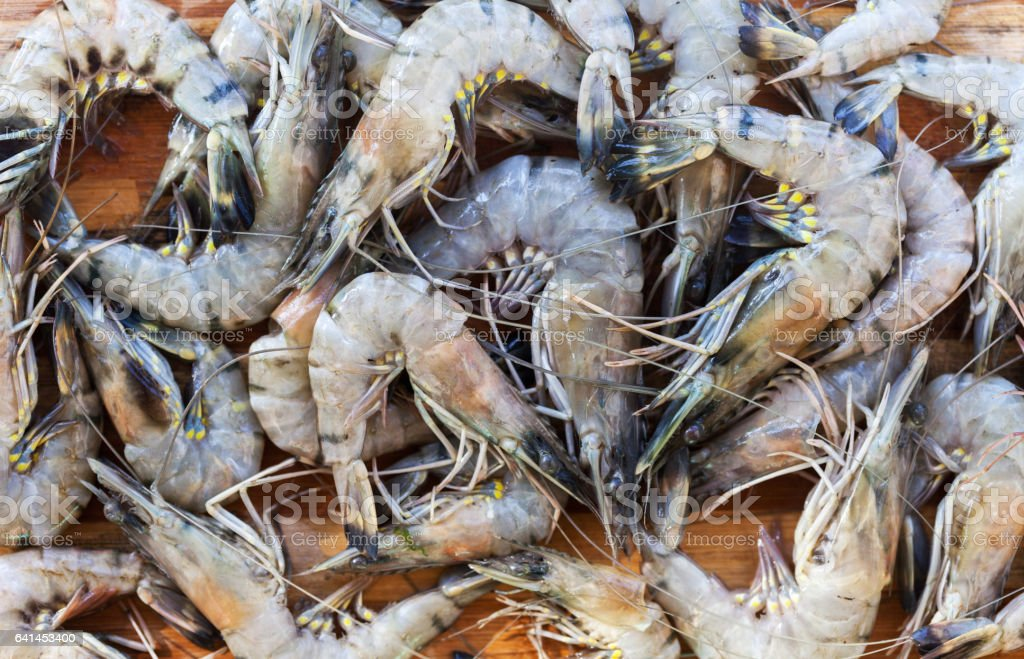 fresh raw shrimps in a bowl on a wooden table stock photo