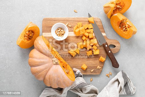 Fresh raw sliced butternut squash on wooden board, top down view