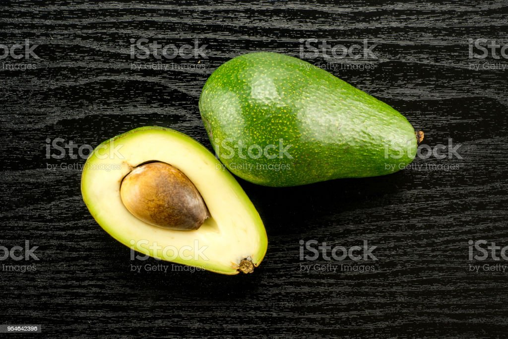 Fresh Raw smooth avocado on black wood stock photo