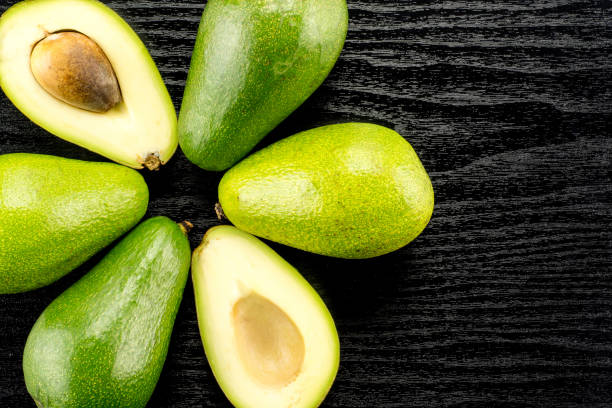 Fresh Raw smooth avocado on black wood stock photo
