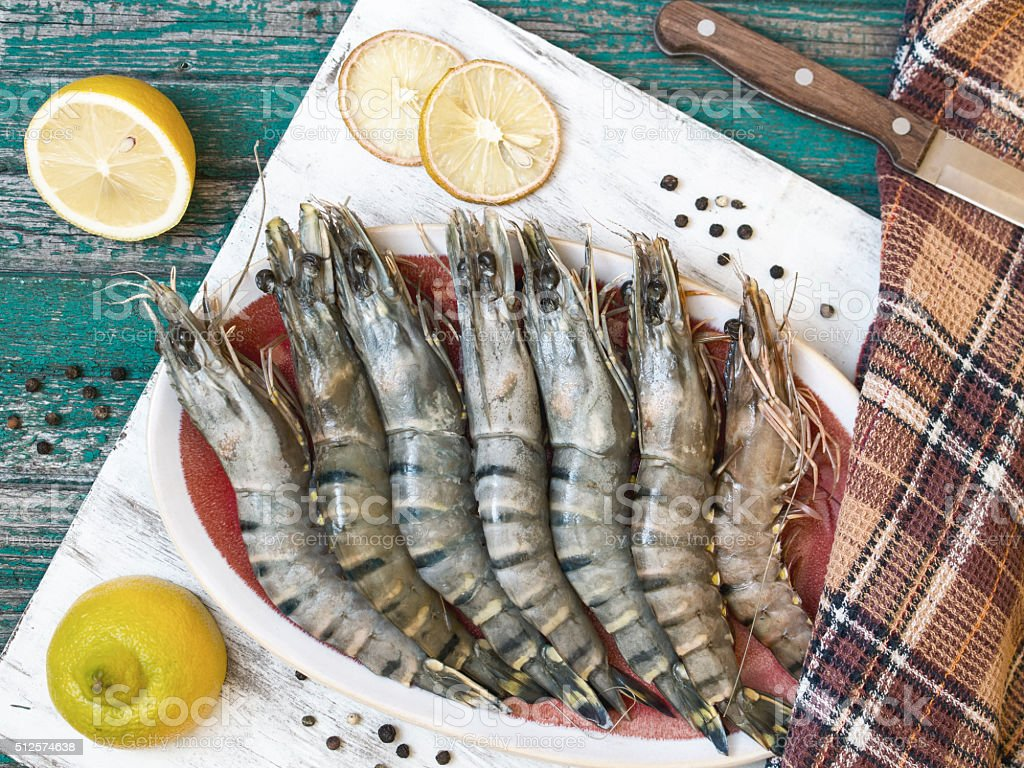 Fresh raw tiger prawns and spices on wooden table stock photo