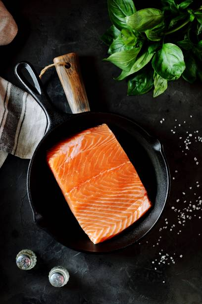 Fresh raw uncooked salmon in a cast iron pan on a black background. Healthy food. Top view. stock photo