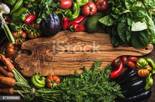istock Fresh raw vegetable ingredients for healthy cooking or salad making with rustic olive wood board in center 673399560