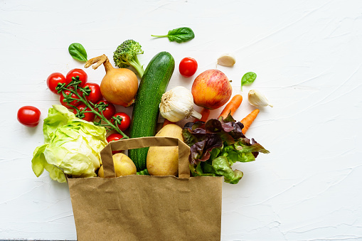 Fresh raw vegetable variation in a paper shopping bag on a white background, top view