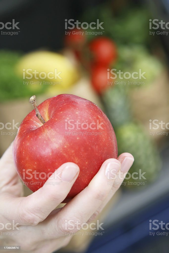 Fresh Red Apple in front of grocery bags royalty-free stock photo