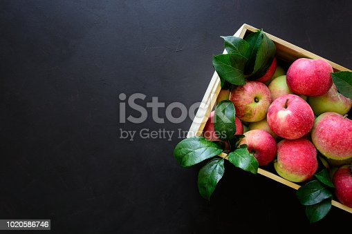 1020586746istockphoto Fresh red apples in the wooden box on black background.  Top view. Copy space 1020586746