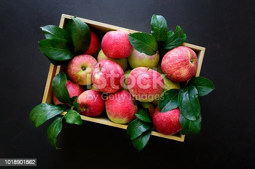 1020586746istockphoto Fresh red apples in the wooden box on black background.  Top view. 1018901862