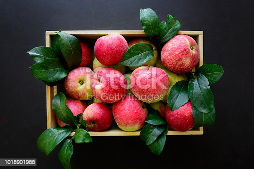 1020586746istockphoto Fresh red apples in the wooden box on black background.  Top view. 1018901988