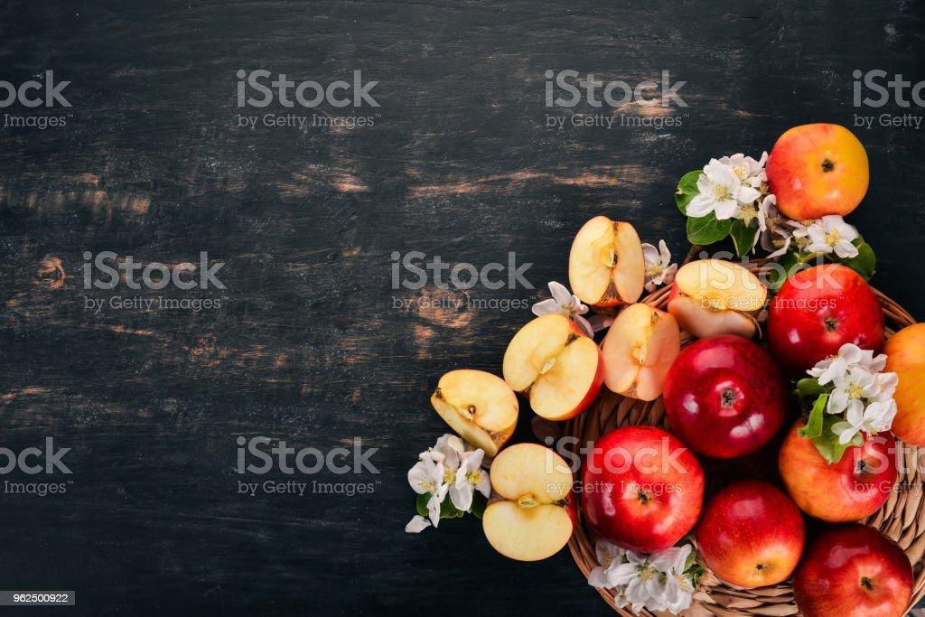 Maçãs vermelhas frescas com inflorescências e folhas. Sobre um fundo de madeira. Vista superior. Copie o espaço. - Foto de stock de Beleza royalty-free