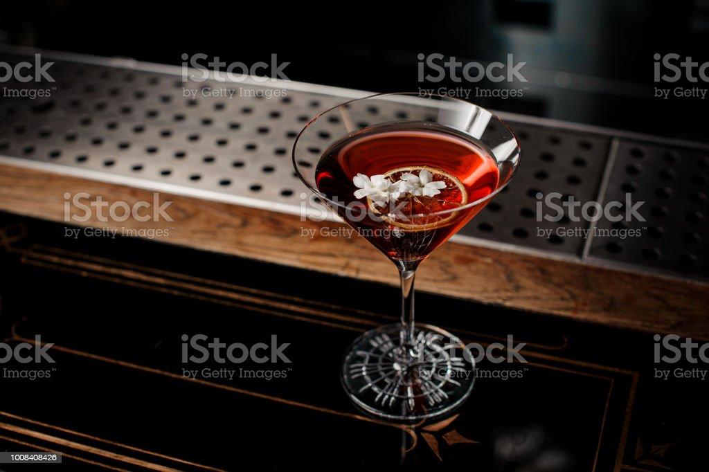 Frische rote Cocktail mit getrockneten Orange und kleine weiße Blume verziert – Foto