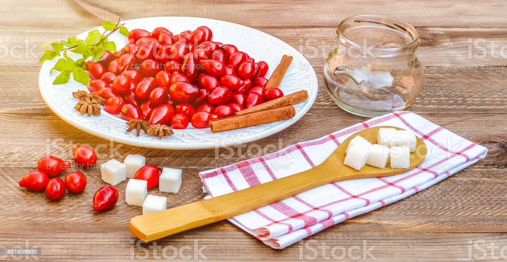 Fresh red cornel berries on white plate, preparing for homemade cornelian cherry jam, surrounded by jelly jar, flax napkin, vintage spoon, sugar. stock photo