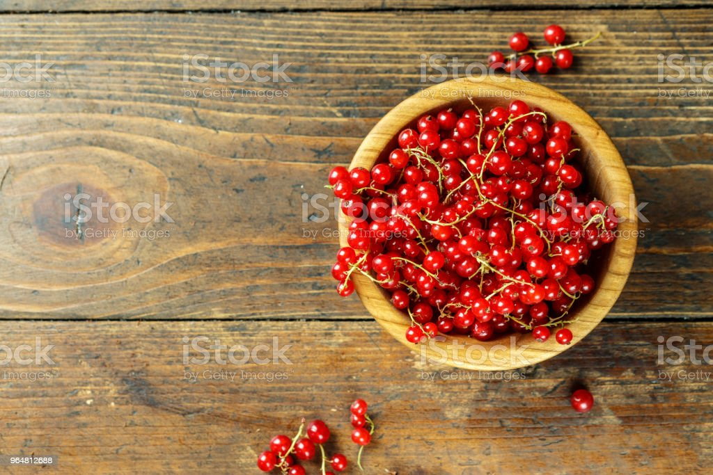 fresh red currant on a wooden background in a wooden plate. royalty-free stock photo