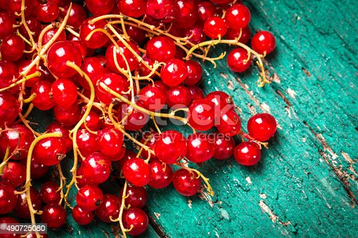 904734850istockphoto Fresh red currant on wooden table 490725080