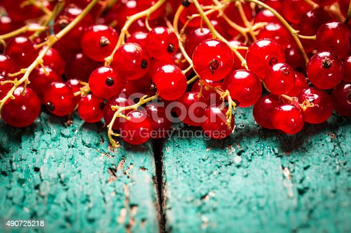 904734850istockphoto Fresh red currant on wooden table 490725218