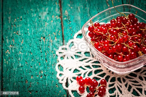 904734850istockphoto Fresh red currant on wooden table 490725316