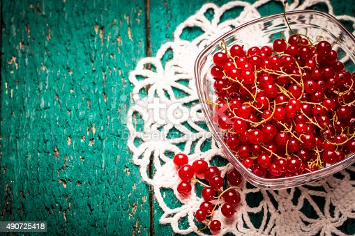904734850istockphoto Fresh red currant on wooden table 490725418